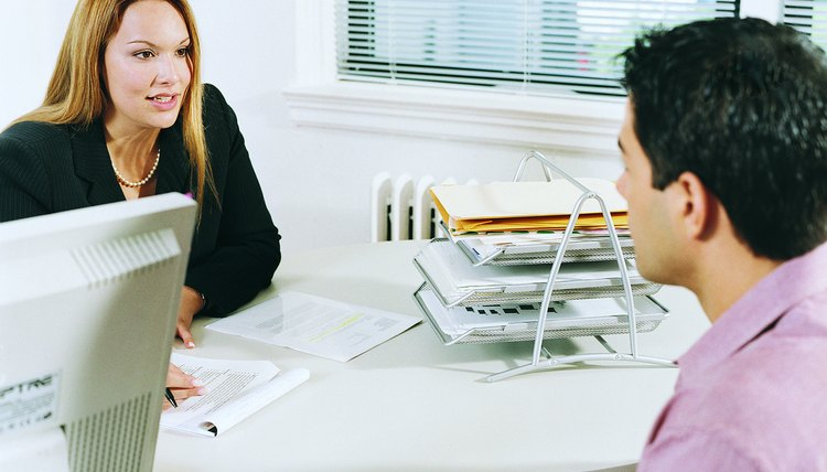 Businesswoman Interviewing a Man in an Office