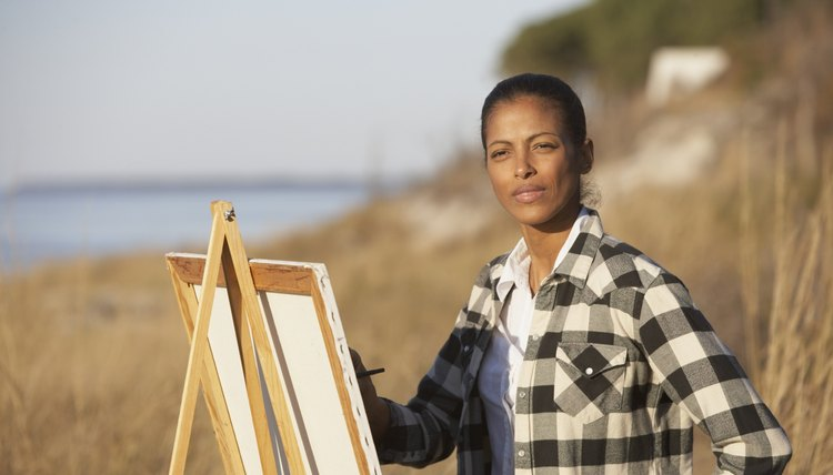 African woman painting at an easel outdoors
