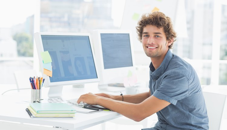 Smiling casual young man using computer in office