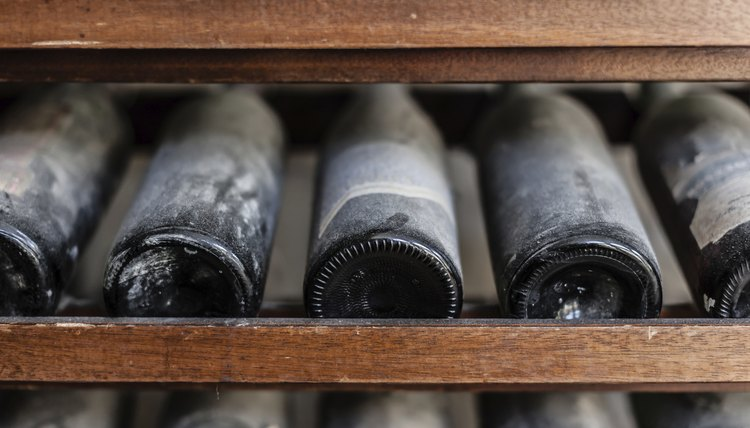 A close-up of antique wine bottles on a shelf in a cellar.