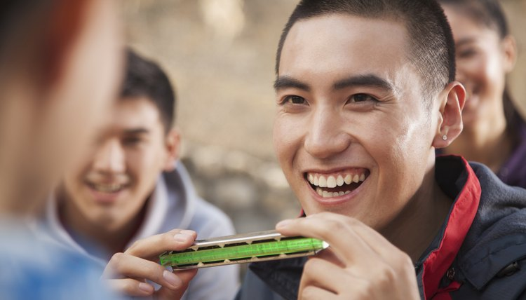 Smiling young man holds a harmonica.