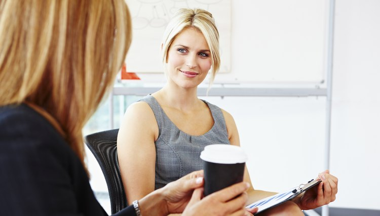 Female business mentor helping client with reports