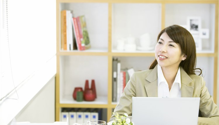 Businesswoman sitting in office using laptop
