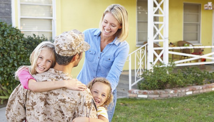 Soldier and family embracing in front of their house
