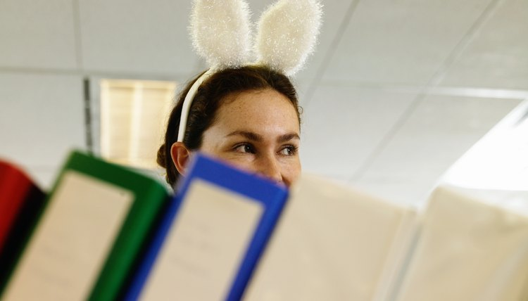 Young woman wearing bunny ears in office, folders in foreground