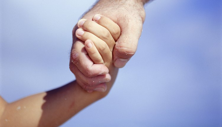 Father and son (4-5) holding hands, Close-up of hands