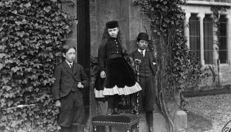 Three children in proper Victorian garb stand outside their home in 1880.