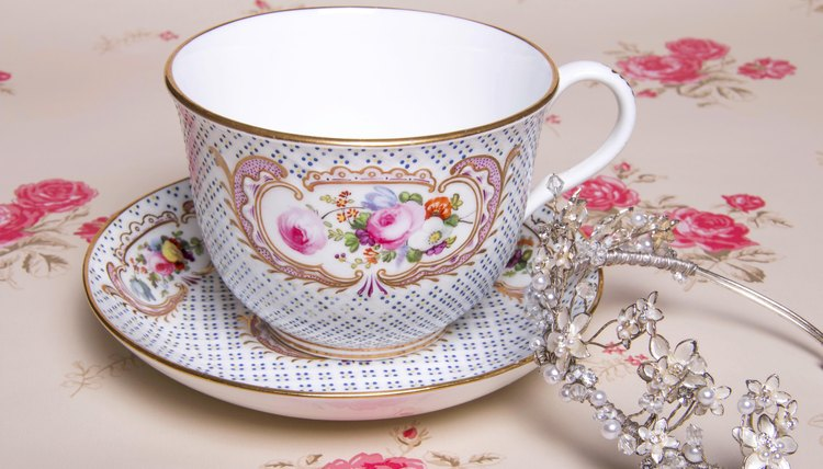 A close-up of a tiara leaning against a tea cup on a tablecloth.