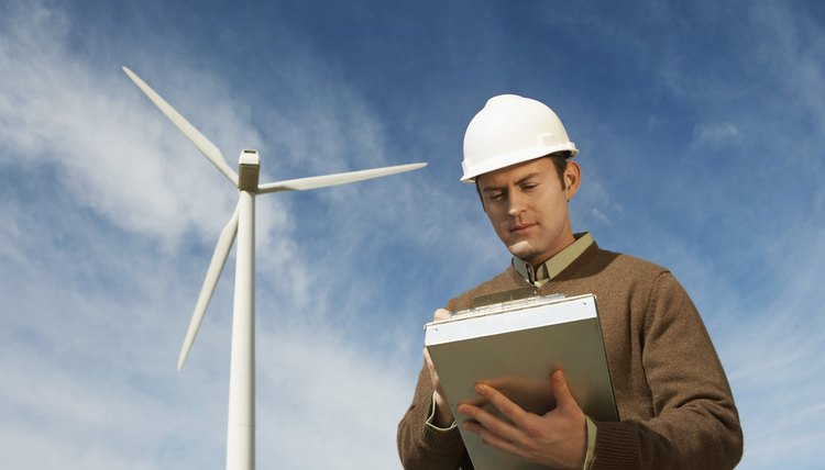 Engineer working near wind turbine at wind farm