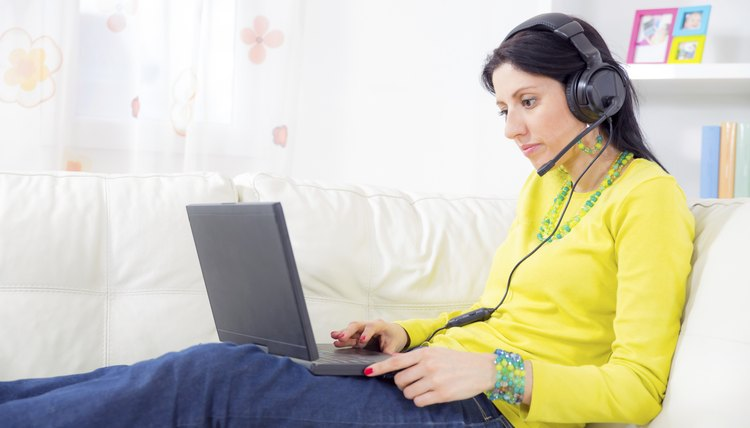 woman on sofa using laptop and headset at home