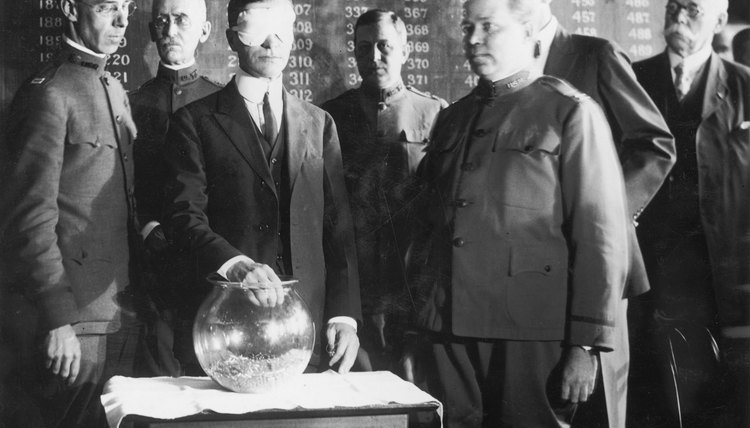 Blindfolded Secretary of War Newton Baker pulls name from glass bowl at the start of World War One