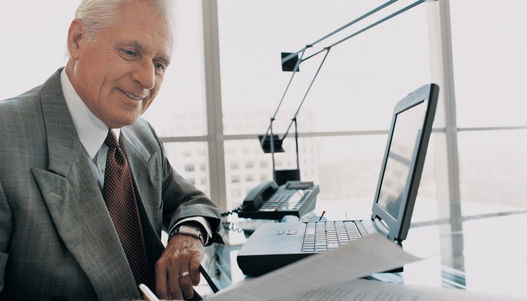 Mature Businessman Looking at Paperwork Sitting at His Desk