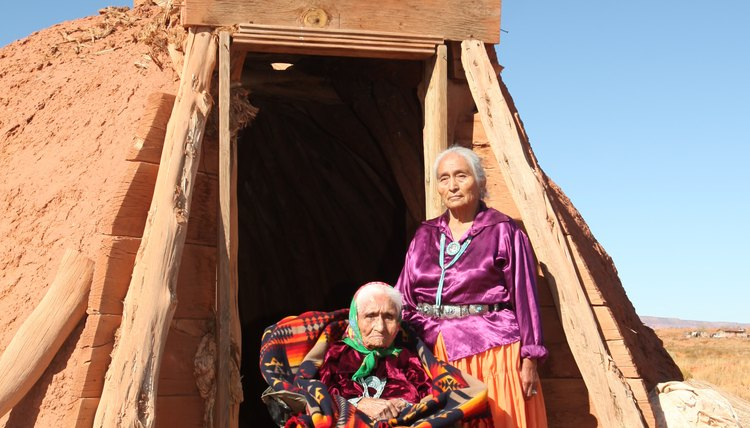 Two elderly Navajo women outside the entrance to a hut