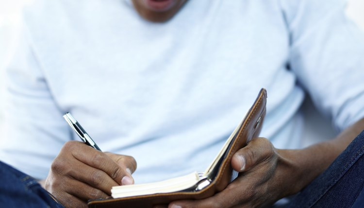 A close-up of a man writing in a notebook.