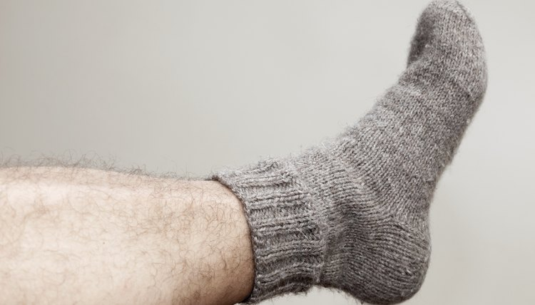 Closeup photo of male foot with gray woolen sock