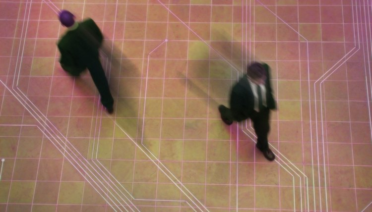 high angle shot of two business men as they walk through their office atrium