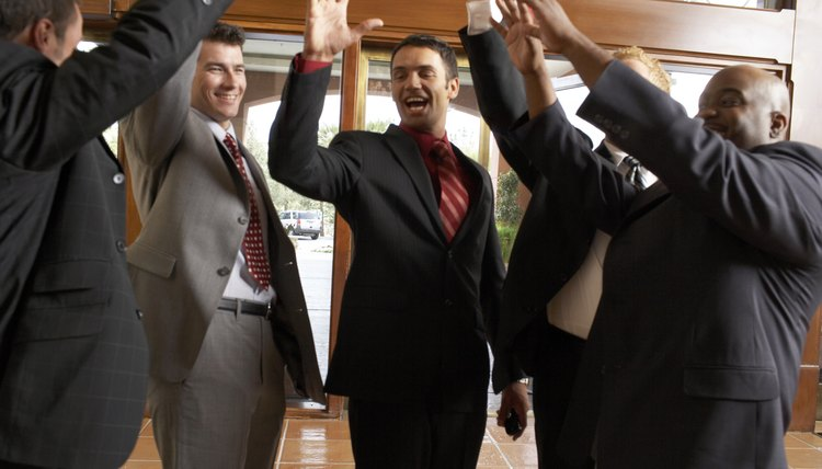 Business men high fiving in hotel foyer, low angle view