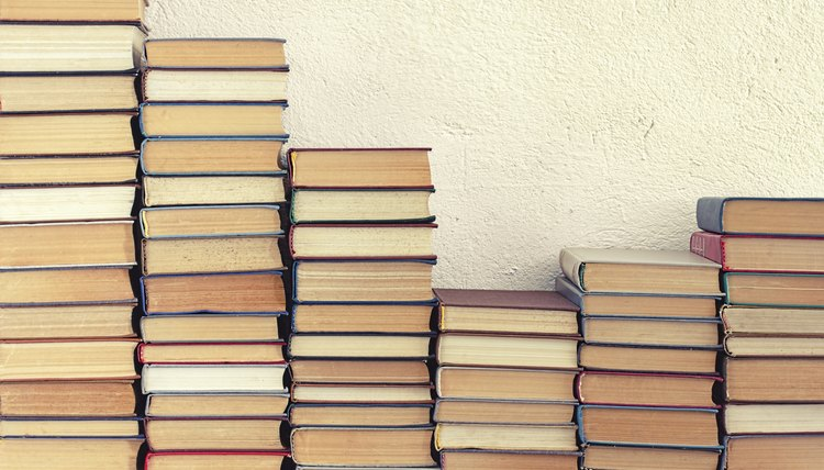 Piles of books leaning against a wall.