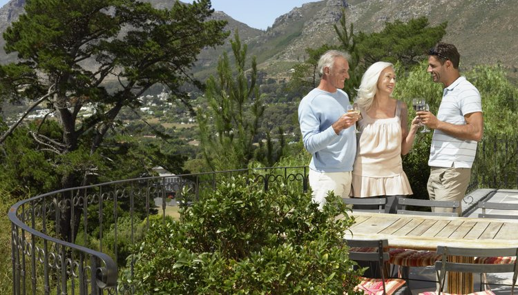 Senior Couple Having a Toast of White Wine With Their Son on the Balcony of Their Holiday Home