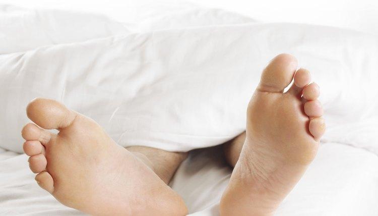 Man's Feet Underneath a Duvet in Bed