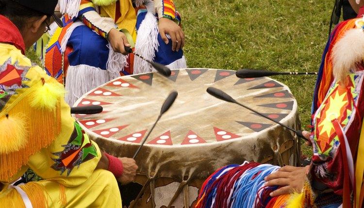 Several tribesmen beat a ceremonial drum