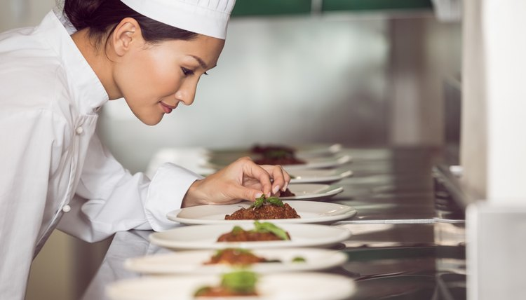 Concentrated female chef garnishing food in kitchen