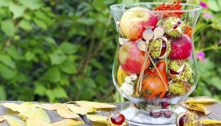 A glass vase filled with seasonal fruit and flowers.