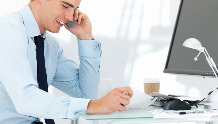 Businessman using cellphone at office desk