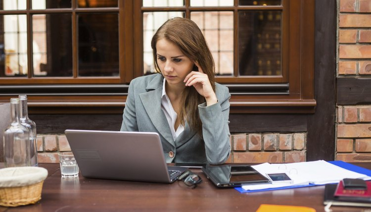 Hard working businesswoman in restaurant with laptop.