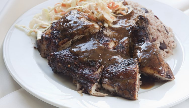 A plate of jerk chicken with rice, beans and coleslaw.
