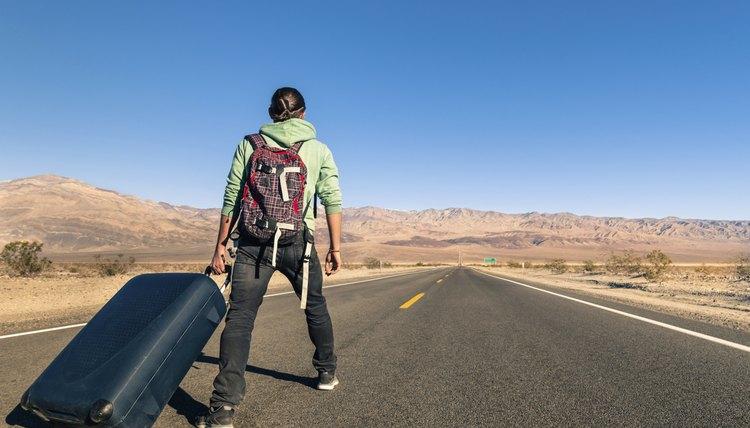 A hobo traveller is walking on an empty road.