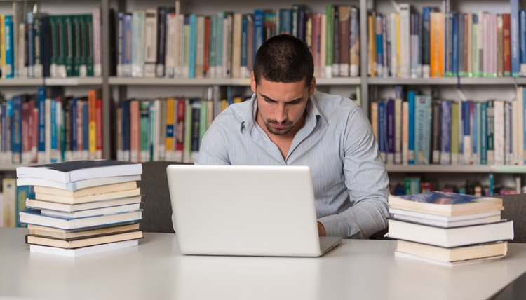 A university student typing on his laptop in a library.