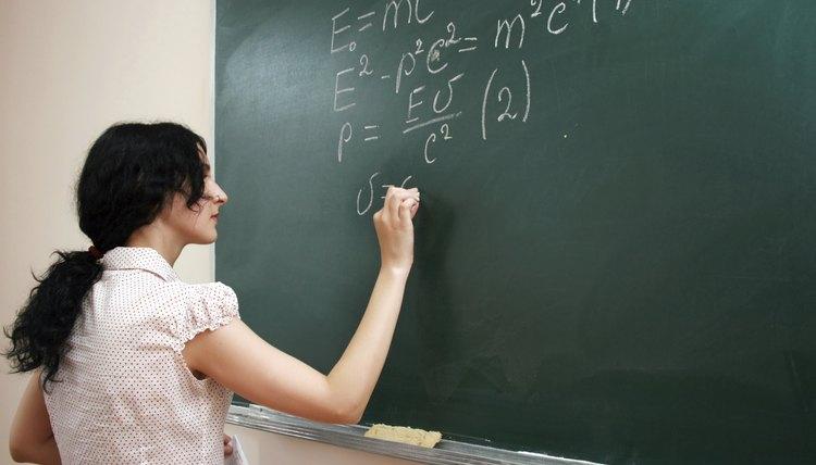 A teacher writes equations on a chalkboard.