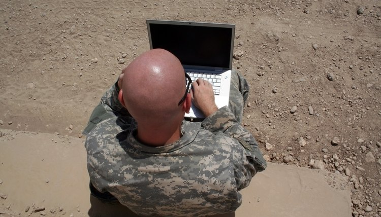 A military man is on a computer.