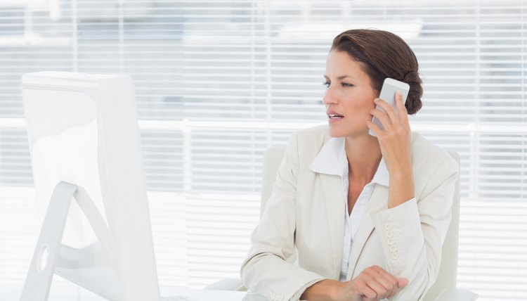 Businesswoman using computer and cellphone at desk