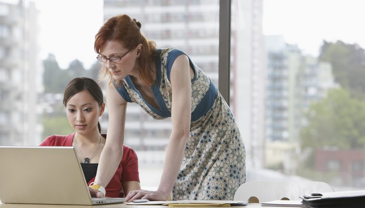 Two women using laptop in office