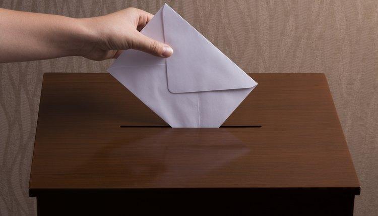Hand casting ballot into box.
