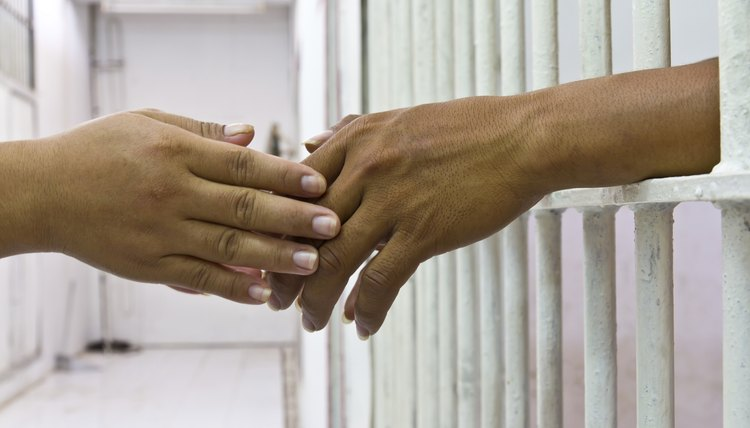 Close-up of two hands touching through prison bars