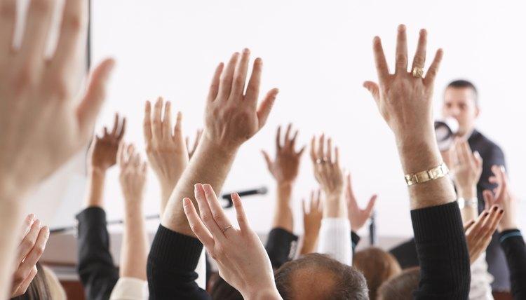 People raising hands in meeting.