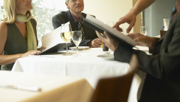 Business People With Menus In Restaurant Waiter Making Recommendation