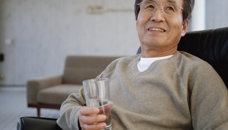 Senior man sitting on armchair holding glass of water, looking up