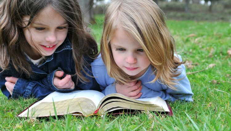 Two young girls reading the Bible on grass