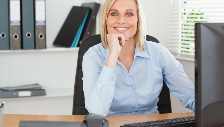 Smiling woman with chin on hand behind a desk