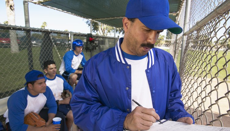 Sports Coach Writing on a Clipboard in a Dugout and Team Watching