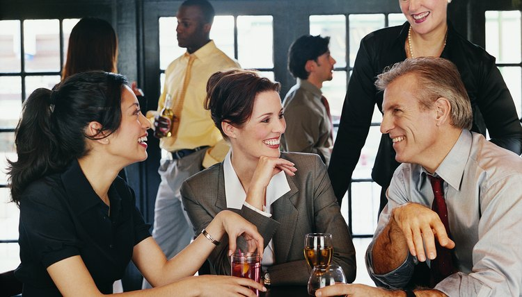 Businesswomen and a Businessmen Enjoying a Drink in a Pub