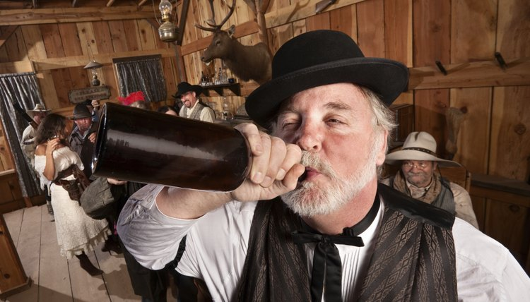 A man in Wild West dress drinking from a bottle, in front of others wearing Wild West costumes.
