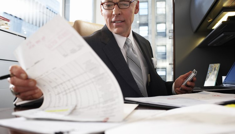 Businessman at desk looking at paperwork, low angle view