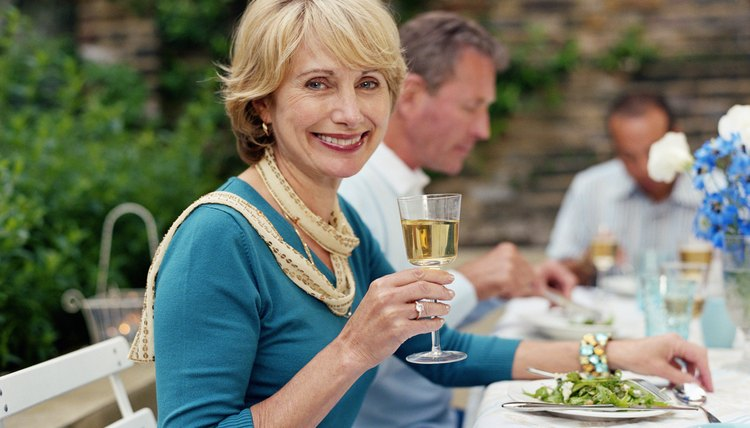Mature woman at lunch table outdoors, by friends, smiling, portrait