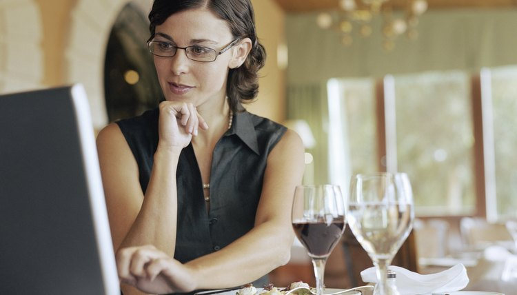 Businesswoman using laptop at restaurant table (Digital Composite)