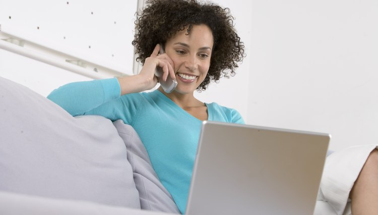 Woman on sofa using laptop computer and mobile phone, smiling